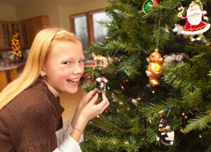 photo: smiling daughter decorates holiday tree