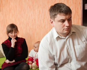 photo: baby sits by troubled parents contemplating separation