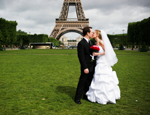 photo: American and French bride and groom at Eiffel tower in Paris