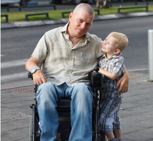 photo: young boy with disabled father in wheelchair